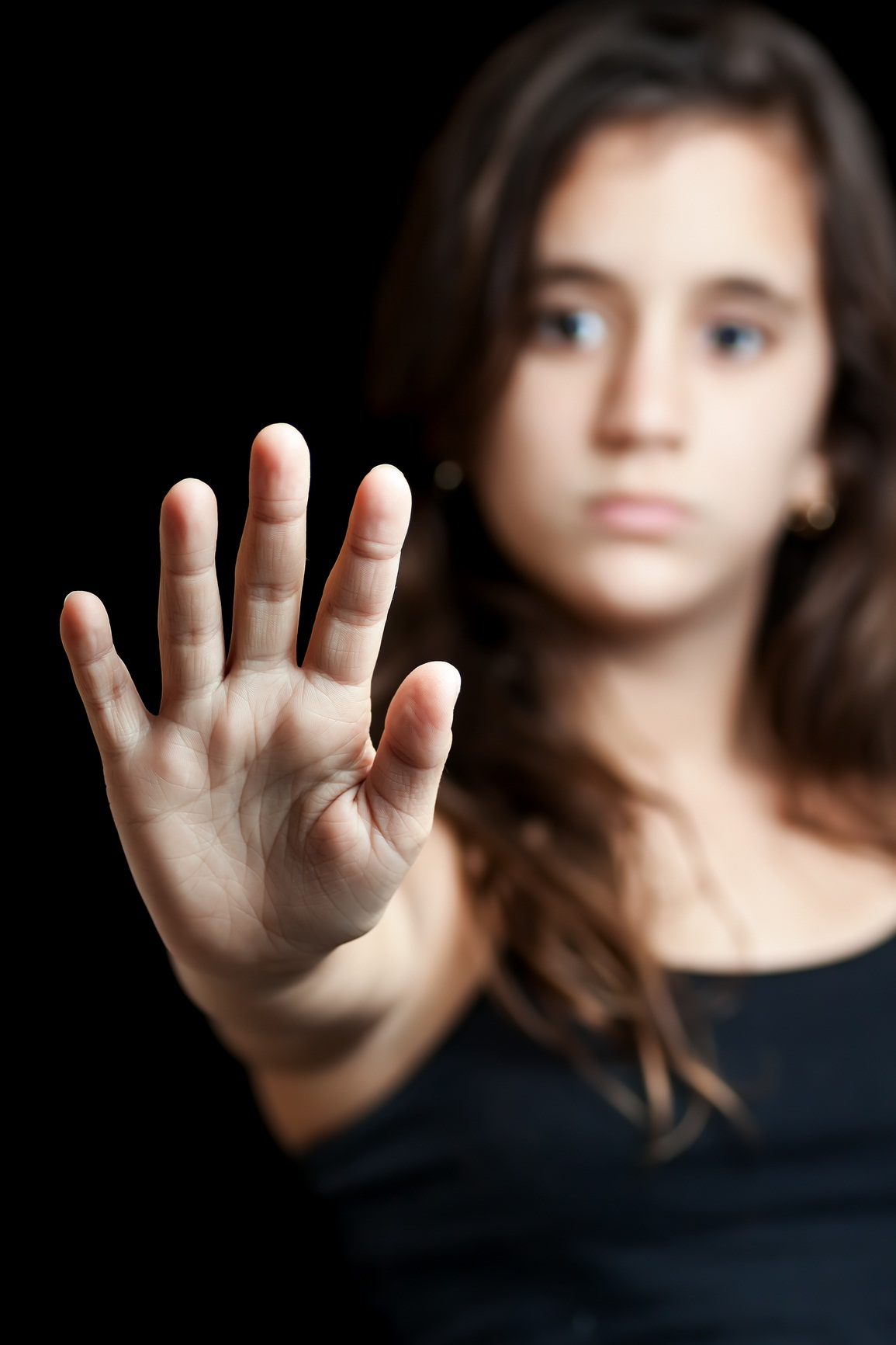 Hispanic girl with her hand extended signaling to stop useful to campaign against violence, gender or sexual discrimination (Focused on her hand)