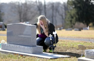 Ashley McLaughlin lays her hand upon the newly placed gravestone for the three Pilkington boys who were killed by their mother.  The stone was donated by Modlich Monuments of Columbus and was put in place on December 11, 2015. (Chris Russell/Dispatch Photo)