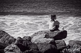 Woman enjoying a cup of coffee in solitude overlooking the Pacific Ocean